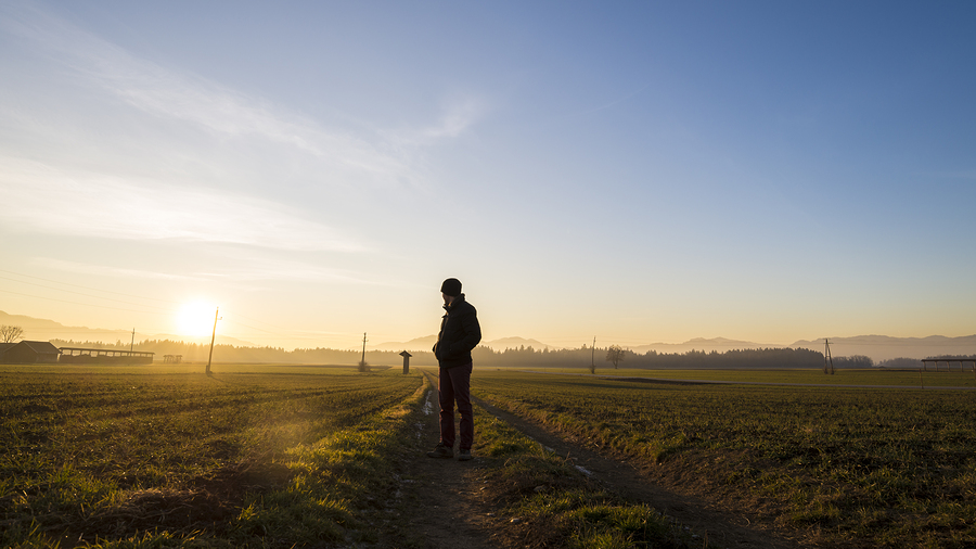 Young Man Standing On Country Road In A Beautiful Landscape Look