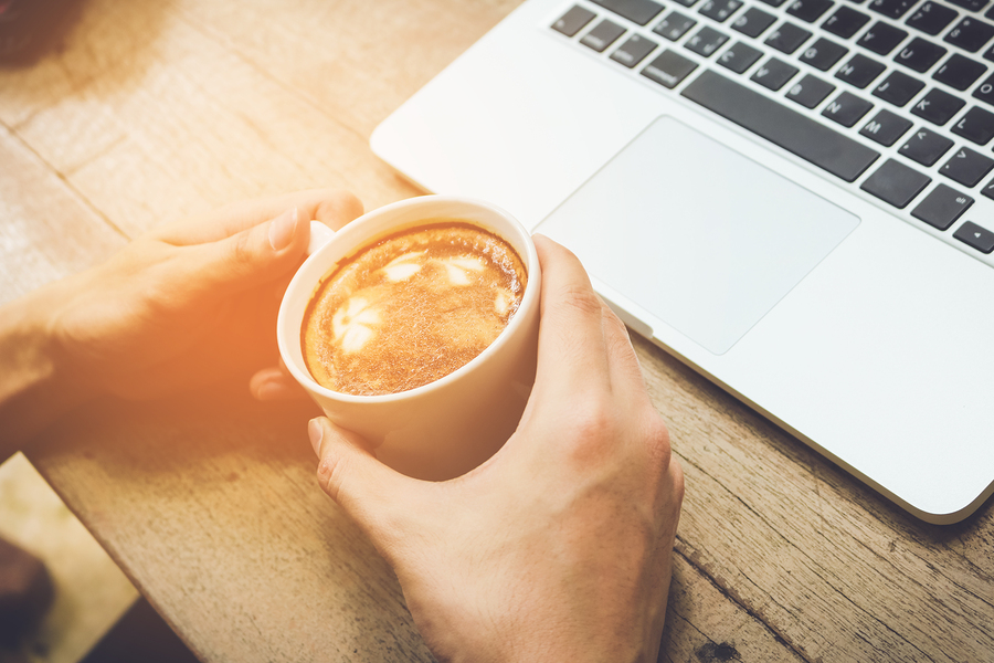 Man holding coffee cup with laptop vintage tone.