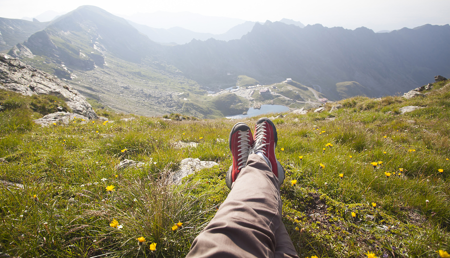 Legs of traveler sitting on a high mountain top in travel. Freed